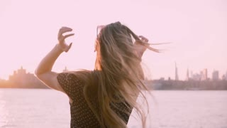 Back view of happy girl standing alone, watching amazing sunset on river shore, touching hair and arms open slow motion.