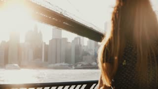 Back view of happy tourist girl with flying hair enjoying Brooklyn Bridge view in New York from embankment, arms open.