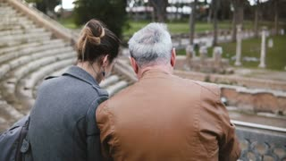 Back view of happy young European girl sitting together with older man talking at ruins of Ostia amphitheater in Italy.