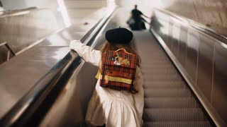 Back view of little cute girl moving upstairs on the escalator. Child clothing the french style going to school.