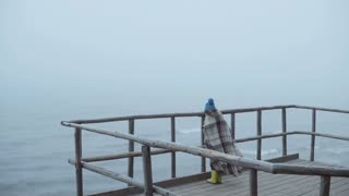 Back view of little girl in rubber boots and plaid standing on wooden pier near the sea. Alone child in foggy windy day.