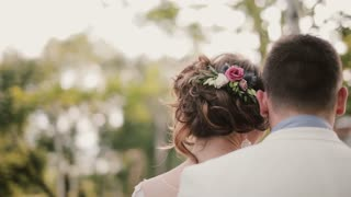 Back view of lovers leaning on each other. Close-up of their heads. Bride with a beautiful hair-do with flowers.