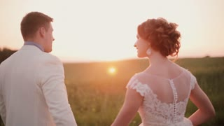Back view of lovers walking in a field at sunset, happily enjoying their wedding day. Bride in a beautiful white dress.