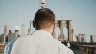 Back view of male tourist walking along Brooklyn Bridge in New York City 4K. Wanderlust, tourism and freedom concept.
