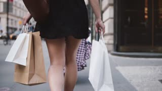 Back view of successful young girl addicted to shopping carrying bags in both hands walking along the street slow motion