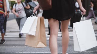 Back view of successful young woman in short black dress carrying shopping bags while crossing the street slow motion.