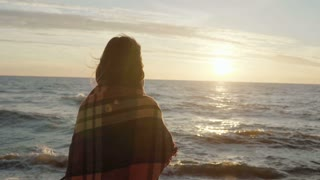 Back view of the brunette woman standing on the shore of sea and dreaming. Young female enjoying the beach and sunset.
