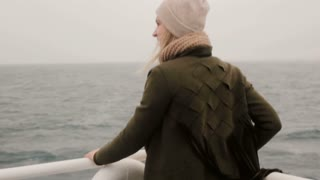 Back view of the tourist woman standing aboard a ferry and looking around. Female enjoying the view.