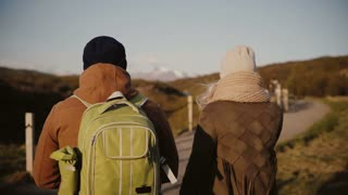 Back view of traveling young couple walking on the nature, valley. Man and woman hiking in Iceland in sunny day.