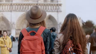 Back view of two traveling woman with backpack walking near the Notre Dame, famous cathedral in Paris, France.