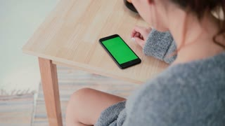Back view of woman sitting at the table in kitchen at home. Brunette girl uses smartphone, green screen.