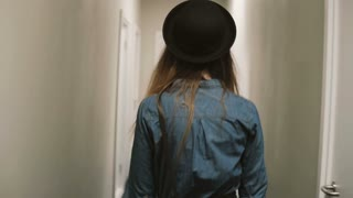 Back view of woman walking through corridor, come in room and puts on knob the door hanger, asking do not disturb her.