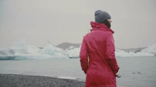 Back view of young attractive woman walking in ice lagoon. Pensive female exploring the famous sight in Iceland alone.