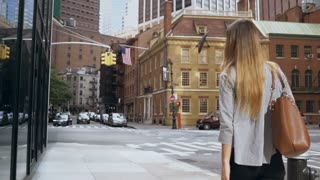 Back view of young beautiful businesswoman going to work in New York, USA and looking on window of office. Slow motion.