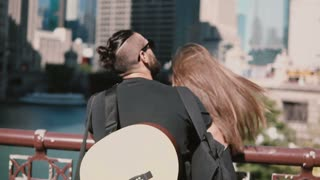Back view of young beautiful couple standing on the bridge, enjoying the view of Chicago, America. Man with guitar.