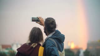 Back view of young beautiful couple taking pictures of city centre landscape, sunset and rainbow on smartphone.