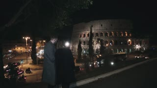 Back view of young beautiful couple walking in evening near the Colosseum in Rome, Italy, talking photos on smartphone.