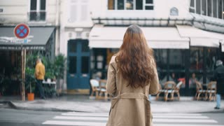 Back view of young beautiful woman crossing the road in Paris, France. Stylish female in cloak walking on the street.