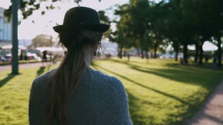 Back view of young beautiful woman in hat walking in the park on sunset and using the smartphone, typing on touchscreen.