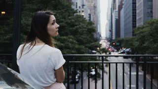 Back view of young beautiful woman standing on the bridge and looking on the traffic road in New York, America.