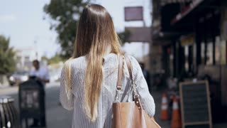 Back view of young beautiful woman walking through the city centre in New York, America. Slow motion.