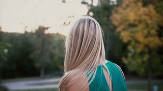 Back view of young blonde woman in park on sunset. Girl moving her head and hair waving on the wind. Slow motion.
