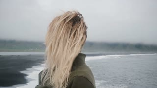 Back view of young blonde woman on the shore of the black beach looking on the troll toes sight in Iceland in windy day.