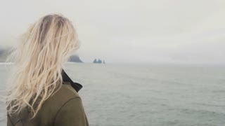 Back view of young blonde woman standing on black beach in iceland. Freedom: tourist rising up hands, hair wave on wind