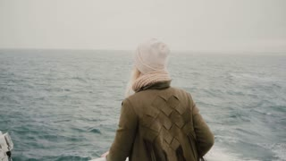 Back view of young blonde woman standing on the ship and looking wistfully on the sea, exploring the Iceland.