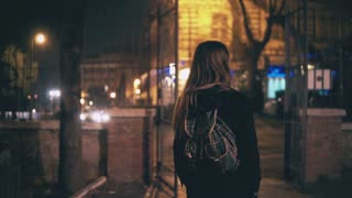 Back view of young brunette woman walking late at night in Rome, Italy city centre. Girl turns and see the Colosseum.