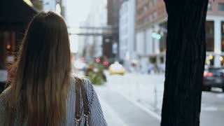 Back view of young brunette woman walking through the street of New York, America. Hair waving on wind. Slow motion.