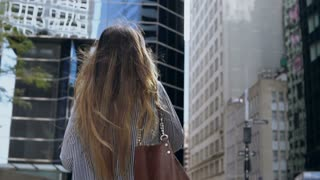 Back view of young businesswoman talk on mobile phone and going to work in financial district in New York. Slow motion
