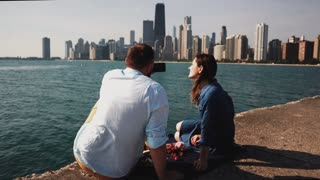 Back view of young couple having picnic on the shore of Michigan lake in Chicago, America. Man takes photo on smartphone