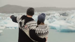 Back view of young couple standing in ice lagoon. Man kisses the woman and hugs her, looking on glaciers in Iceland.