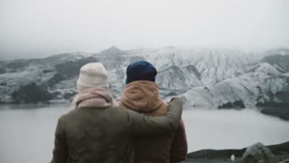 Back view of young couple standing in Ice lagoon. Traveling man and woman exploring the Iceland together.