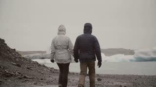 Back view of young couple walking in ice lagoon in Iceland. Man and woman exploring the icebergs and glaciers.