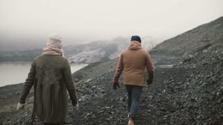 Back view of young couple walking in Ice lagoon. Man and woman hiking in the mountains in Iceland together.