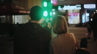 Back view of young hipster couple standing in city centre and listening the concert, musician performance in the evening