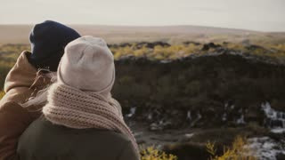 Back view of young man and woman standing in the sunny valley and enjoying the beautiful view in Iceland.