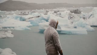 Back view of young man in raincoat standing in ice lagoon in Iceland. Tourist exploring the famous sight alone.