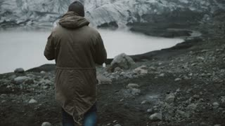 Back view of young man walking in ice lagoon alone. Traveling male hiking in volcanic mountains near glaciers in Iceland