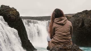 Back view of young pensive woman sitting on a rock alone and looking on powerful waterfall in Iceland.