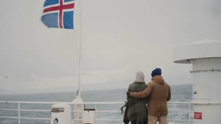 Back view of young stylish couple standing on the board of the ship with Icelandic flag. Man and woman look on the sea.