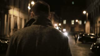 Back view of young stylish man walking late at night through the dark street, going in the evening alone.
