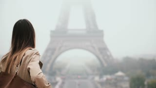 Back view of young stylish woman walking in downtown near the Eiffel tower in Paris, France in foggy morning.