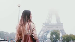 Back view of young stylish woman walking in downtown of Paris, France in early foggy morning and looks on Eiffel tower.