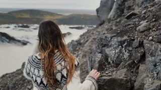 Back view of young tourist woman hiking in mountains through the rocks near the Vatnajokull glacier lagoon in Iceland.
