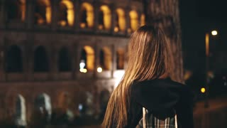 Back view of young tourist woman standing near Colosseum in Rome, Italy and raising hands, looking on building. Slow mo.