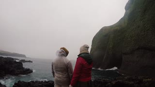 Back view of young tourists couple in raincoats standing on the shore of the sea in foggy day and enjoying the landscape