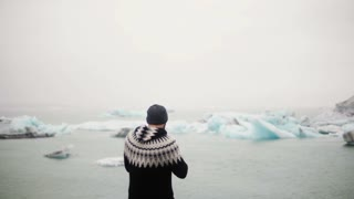 Back view of young traveling man standing in Jokulsalon ice lagoon in Iceland and take photos og glaciers on smartphone.